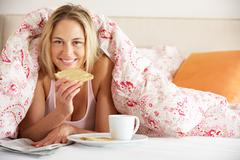 Pretty woman snuggled under duvet eating breakfast and reading newspaper Stock Photos