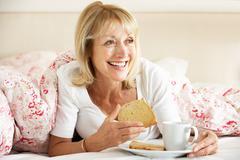 Senior woman snuggled under duvet eating breakfast Stock Photos