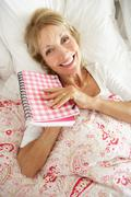 Senior woman relaxing in bed reading diary Stock Photos