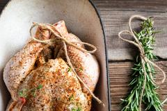 closeup of raw chicken with herbs in casserole dish - stock photo