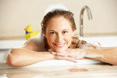 Woman relaxing in bubble filled bath Stock Photos