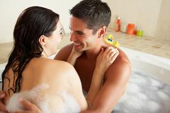 Couple relaxing in bubble filled bath Stock Photos