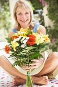Senior woman with bunch of flowers Stock Photos