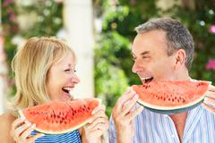 Senior couple enjoying slices of water melon Stock Photos