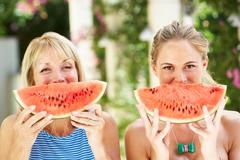 mother and adult daughter enjoying slices of water melon - stock photo