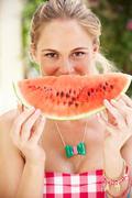 woman enjoying slice of water melon - stock photo