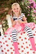 Young girl wearing pink wellington boots drinking milkshake Stock Photos