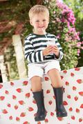 Young boy wearing wellington boots drinking milkshake Stock Photos
