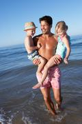 Father and children having fun on beach Stock Photos