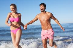 Couple enjoying beach holiday Stock Photos