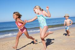 Three children running along beach Stock Photos