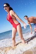 Couple enjoying beach holiday Stock Photos