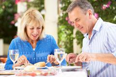 Senior couple enjoying meal outdoorss Stock Photos