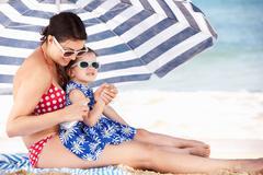 Mother and daughter under beach umbrella putting on sun cream Stock Photos