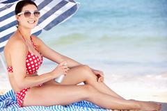 Woman sheltering from sun under beach umbrella putting on sun cream Stock Photos