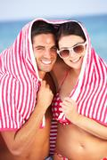 Couple sheltering from sun on beach holiday Stock Photos
