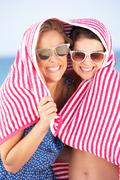 Two women sheltering from sun on beach holiday Stock Photos