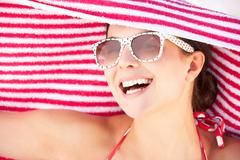 Woman sheltering from sun on beach holiday Stock Photos