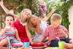 Group of children eating jelly at outdoor tea party Stock Photos