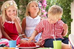 group of children eating jelly at outdoor tea party - stock photo
