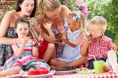 Children and mothers eating jelly and cake at outdoor tea party Stock Photos