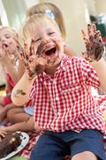 group of children eating cake at outdoor tea party - stock photo