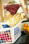 boy sitting in basket sorting laundry on kitchen counter - stock photo