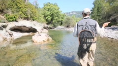 Fisherman fly fishing in trout river Stock Footage