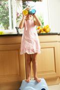 Girl standing on plastic step in kitchen helping with washing up Stock Photos