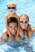 Family having fun in swimming pool Stock Photos