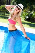 Woman wearing bikini and sarong by swimming pool Stock Photos