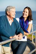 senior man with adult daughter looking over railing at sea - stock photo