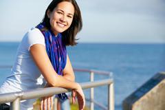 hispanic woman looking over railing at sea - stock photo
