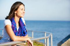 Hispanic woman looking over railing at sea Stock Photos