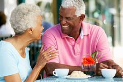 Senior couple enjoying snack at outdoor caf_ Stock Photos