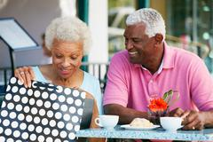 Senior couple enjoying snack at outdoor caf_ after shopping Stock Photos