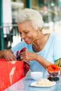 Senior woman enjoying snack at outdoor caf_ after shopping Stock Photos