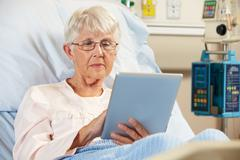 Senior female patient relaxing in hospital bed with digital tablet Stock Photos