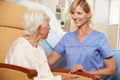Nurse taking to senior female patient seated in chair by hospital bed Stock Photos