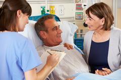 Nurse talking to couple on ward Stock Photos