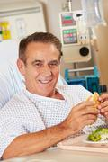 Male patient enjoying meal in hospital bed Stock Photos