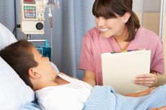 Nurse visiting child patient on ward Stock Photos