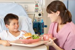 Nurse serving child patient meal in hospital bed Stock Photos