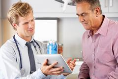 Doctor discussing records with patient using digital tablet Stock Photos