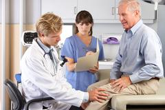Doctor examining male patient with knee pain Kuvituskuvat