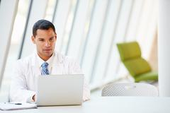 Doctor using laptop sitting at desk in modern hospital Stock Photos