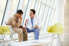 Doctor counselling soldier suffering from stress Stock Photos
