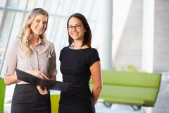 Businesswomen having informal meeting in modern office Stock Photos