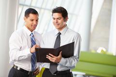 Two businessmen having informal meeting in modern office Stock Photos