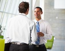 Two businessmen having informal meeting in modern office Stock Photos